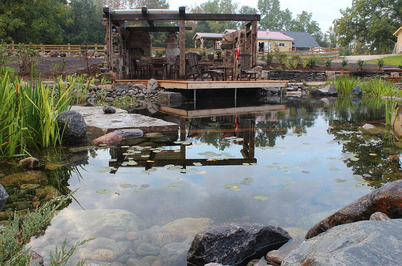 Rustic-natural-pool-with-a-farm-backdrop-and-a-faux-ruin-shelter